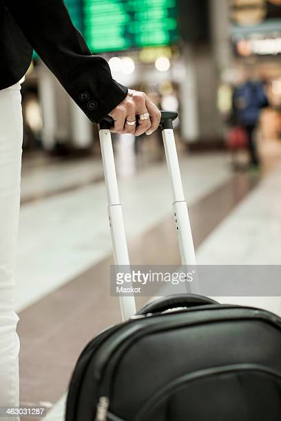 Midsection of businessman carrying bag while standing on railway station