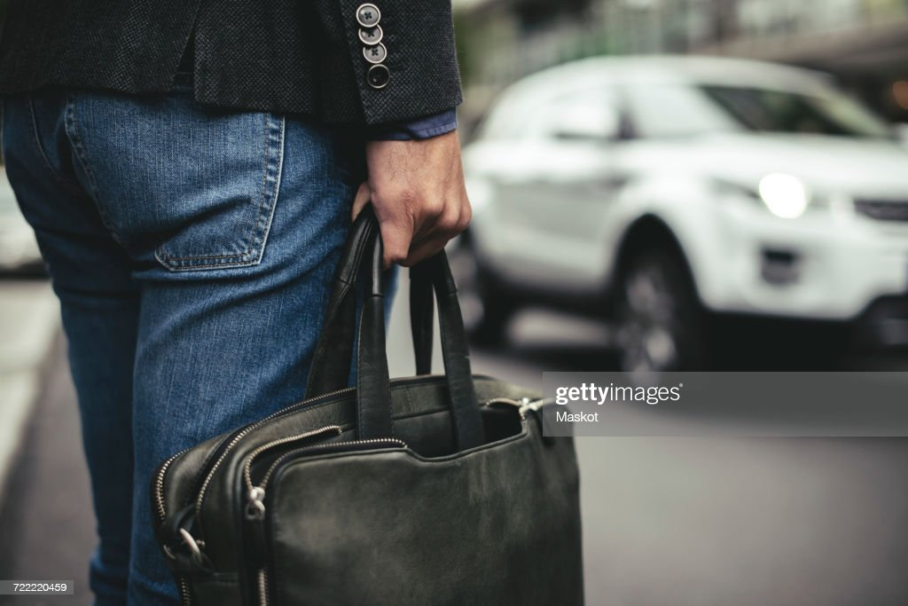 Midsection of businessman carrying briefcase on street : Stock Photo