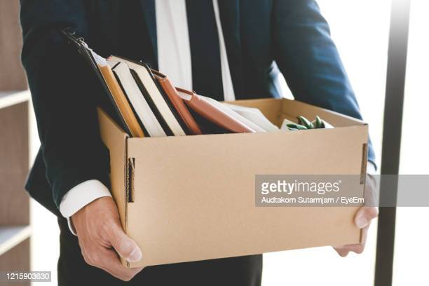midsection of businessman carrying cardboard box in office - quitting a job stock pictures, royalty-free photos & images