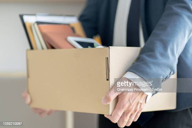 midsection of businessman carrying cardboard box - being fired photos stock pictures, royalty-free photos & images