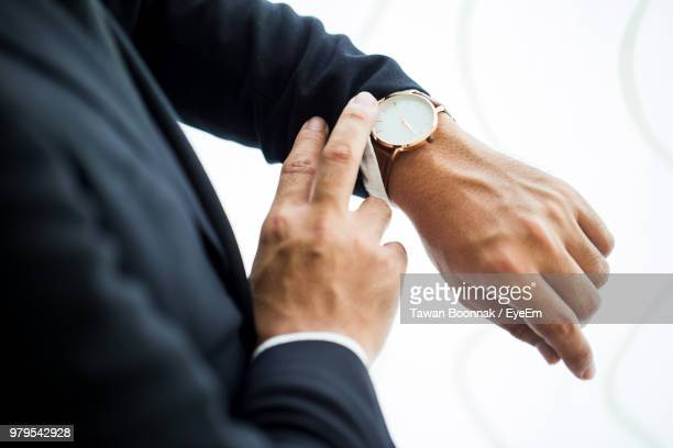 midsection of businessman checking time in office - wrist watch stock pictures, royalty-free photos & images
