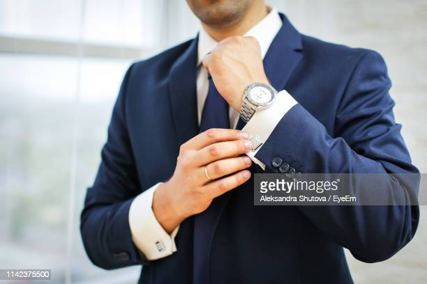 midsection of businessman cuff link shirt sleeve at home - cuff sleeve stock pictures, royalty-free photos & images