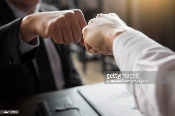 midsection of businessman doing fish bump with colleague in office - fist bump stock pictures, royalty-free photos & images