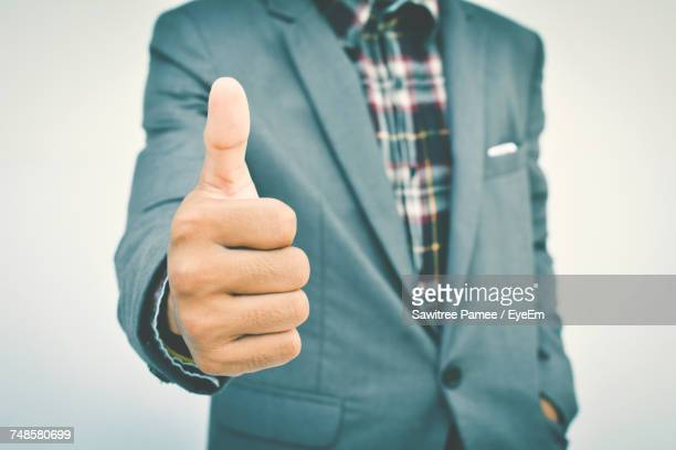Midsection Of Businessman Gesturing Thumbs Up Sign Against White Background