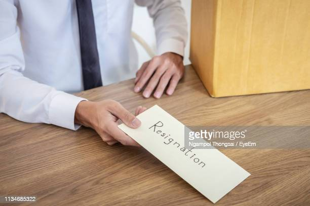 midsection of businessman giving resignation letter in office - quitting a job stock pictures, royalty-free photos & images