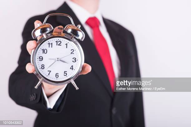 Midsection Of Businessman Holding Alarm Clock Against White Background