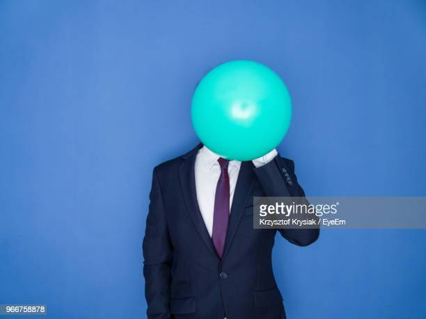 midsection of businessman holding balloon while standing against blue background - obscured face stock pictures, royalty-free photos & images