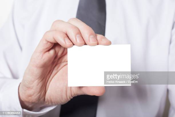 midsection of businessman holding blank card - 名刺 ストックフォトと画像
