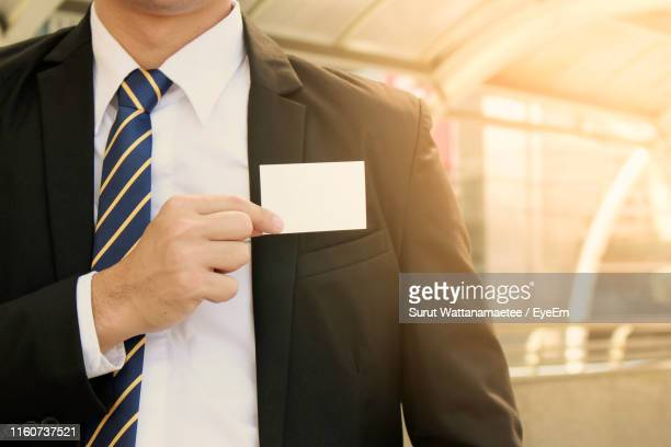 midsection of businessman holding blank paper in suit pocket - pocket stock photos and pictures