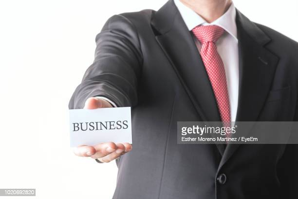 Midsection Of Businessman Holding Business Card Against White Background