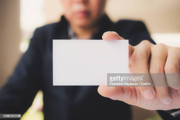 midsection of businessman holding card - 名刺 ストックフォトと画像