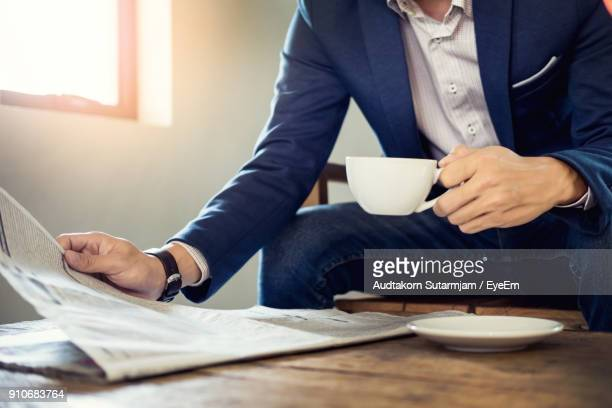 Midsection Of Businessman Holding Coffee While Reading Newspaper On Table