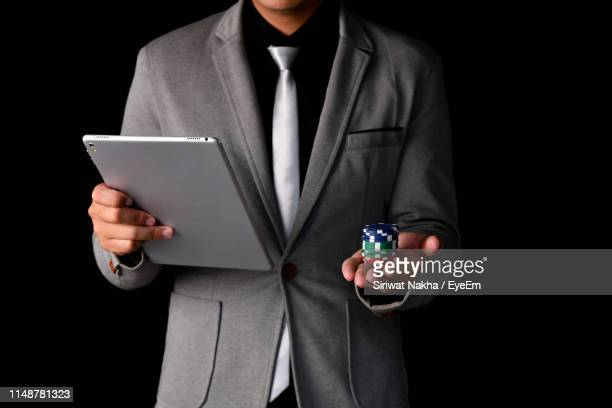 midsection of businessman holding digital tablet and gambling chips against black background - 背広 ストックフォトと画像