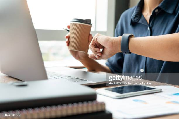 midsection of businessman holding disposable cup while checking time on table - polshorloge stockfoto's en -beelden