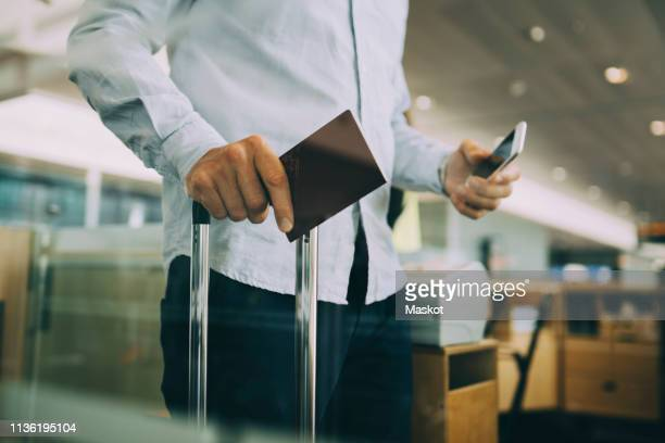 midsection of businessman holding passport and smart phone at airport - passport stock pictures, royalty-free photos & images