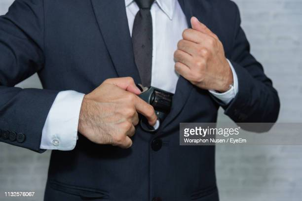 midsection of businessman inserting handgun in blazer - veste noire photos et images de collection