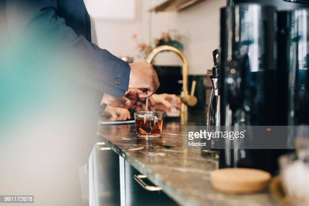 Midsection of businessman making tea while standing at kitchen counter in office