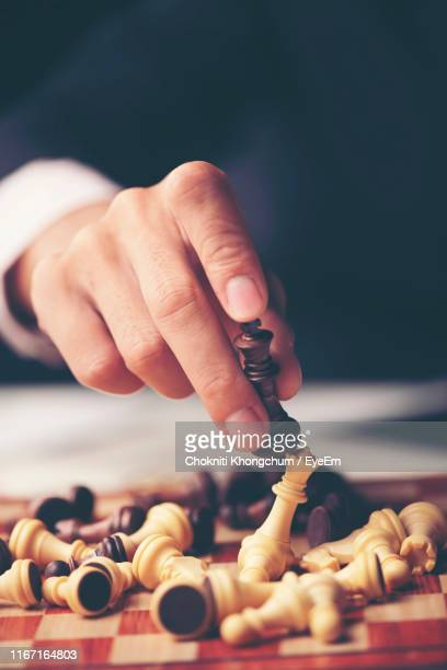 midsection of businessman playing chess on table - king stock pictures, royalty-free photos & images