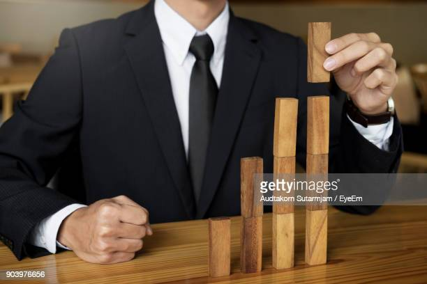 Midsection Of Businessman Playing With Toy Blocks