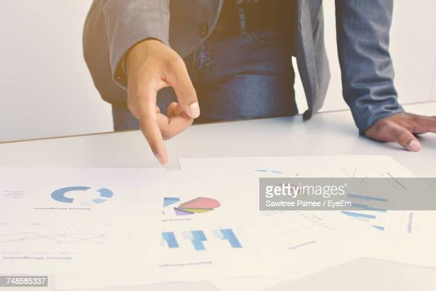 Midsection Of Businessman Pointing Graphs On Table