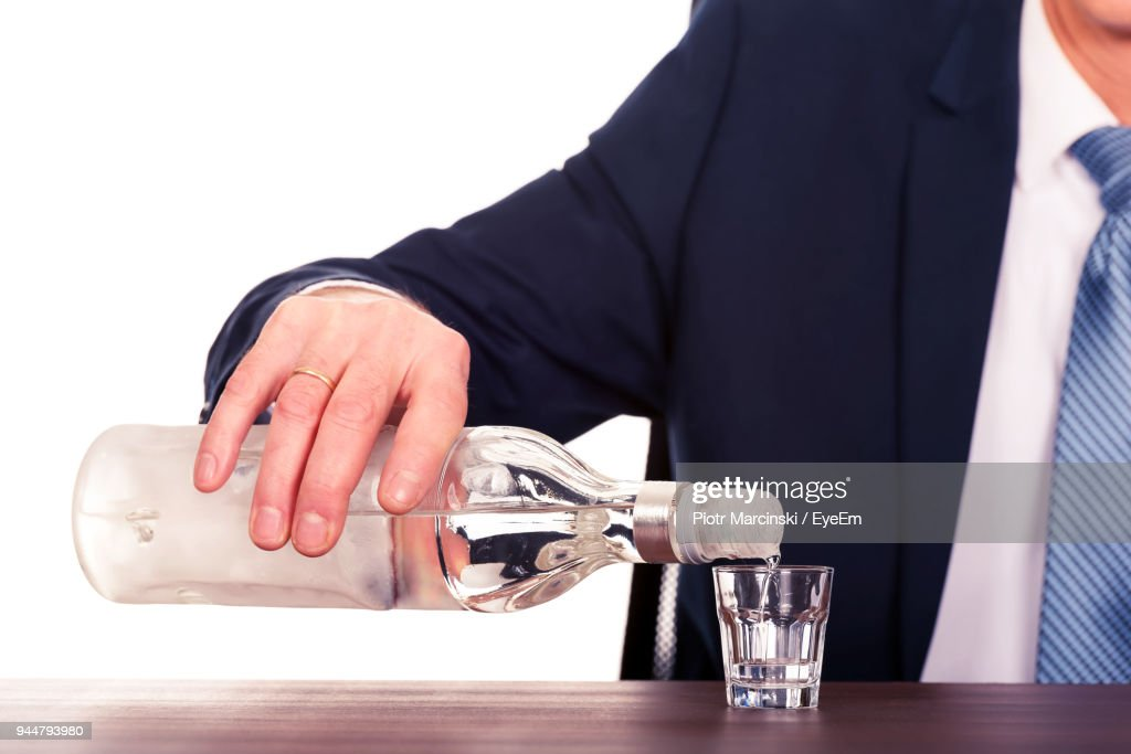 Midsection Of Businessman Pouring Drink Against White Background : Stock Photo