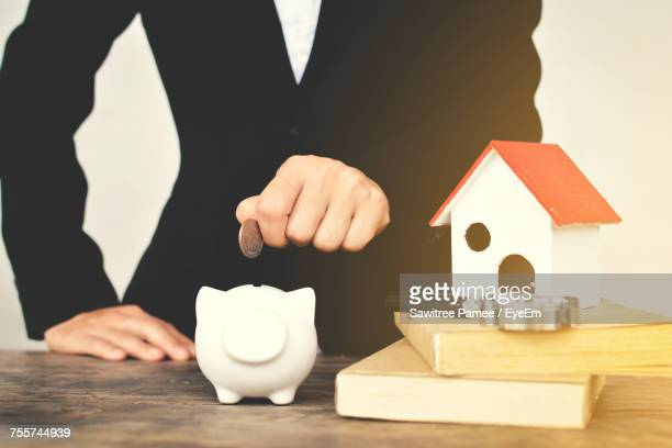 Midsection Of Businessman Putting Coin In Piggy Bank On Table At Office