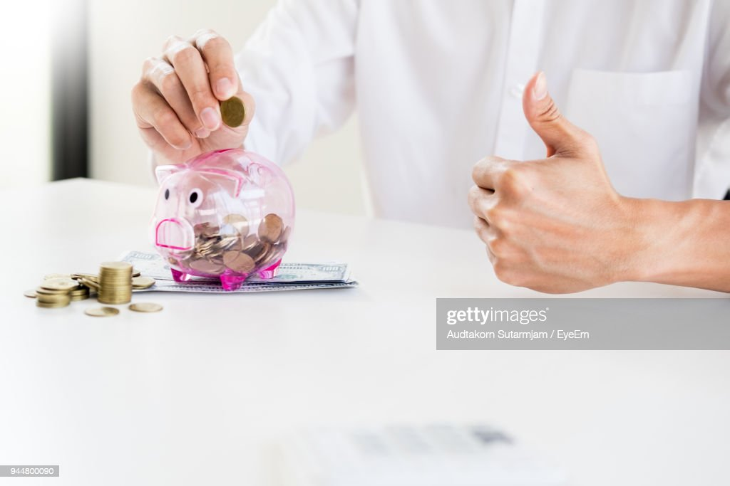 Midsection Of Businessman Putting Coin In Transparent Piggybank At Desk : Stock Photo