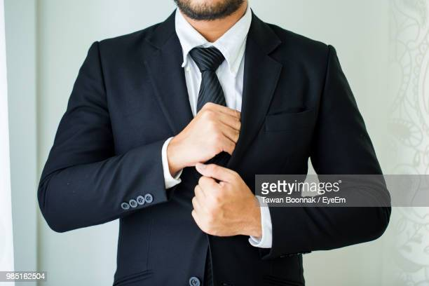 d31cf09dcec0c Midsection Of Businessman Putting Hand In Suit Pocket In Office