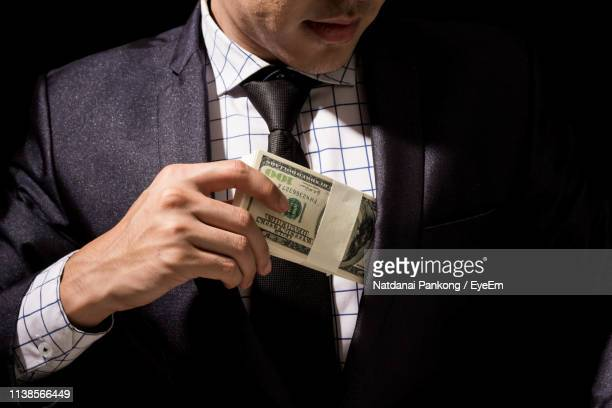 midsection of businessman putting paper currency in pocket against black background - corruption stock pictures, royalty-free photos & images