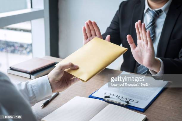 midsection of businessman refusing bribe on table - corruption stock pictures, royalty-free photos & images