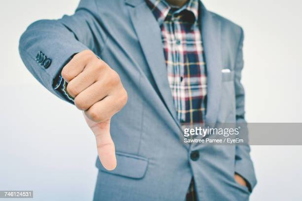 midsection of businessman showing thumbs down sign while standing against white background - dismissal stock photos and pictures