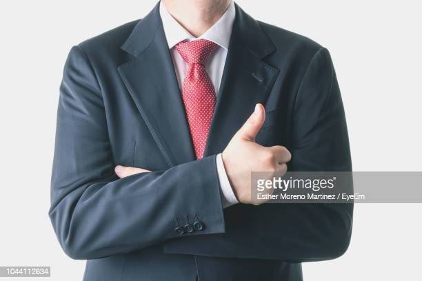 Midsection Of Businessman Showing Thumbs Up Sign Against White Background