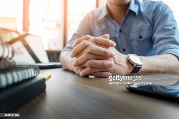 Midsection Of Businessman Sitting At Table In Office