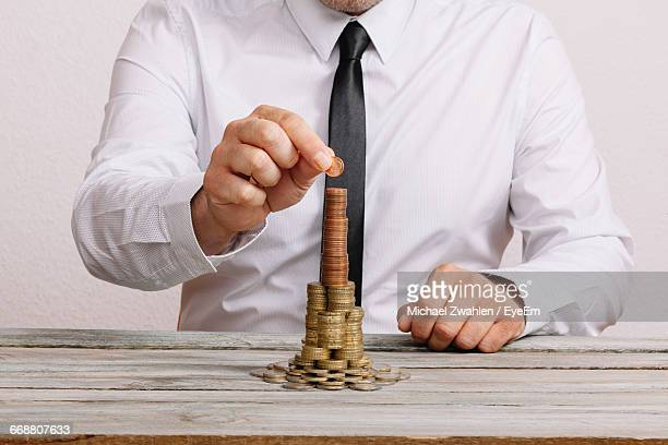 Midsection Of Businessman Stacking Coins On Table