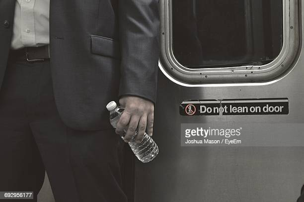 Midsection Of Businessman Standing By Door In Train