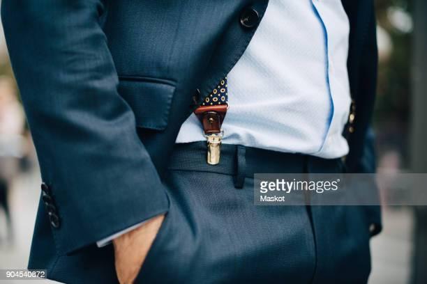 midsection of businessman standing with hand in pocket - handen in de zakken stockfoto's en -beelden
