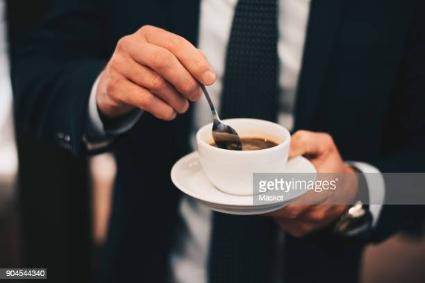 Midsection of businessman stirring coffee from spoon in cafe