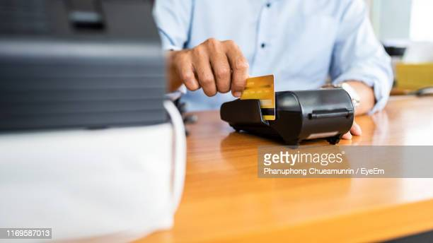 midsection of businessman swiping credit card - money transfer stock pictures, royalty-free photos & images