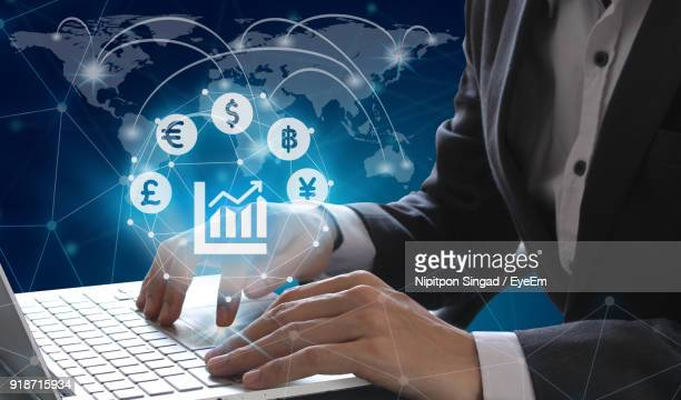 midsection of businessman using laptop against world map - crypto monnaie photos et images de collection