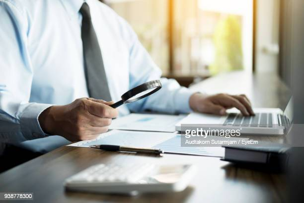 Midsection Of Businessman Using Laptop At Desk In Office