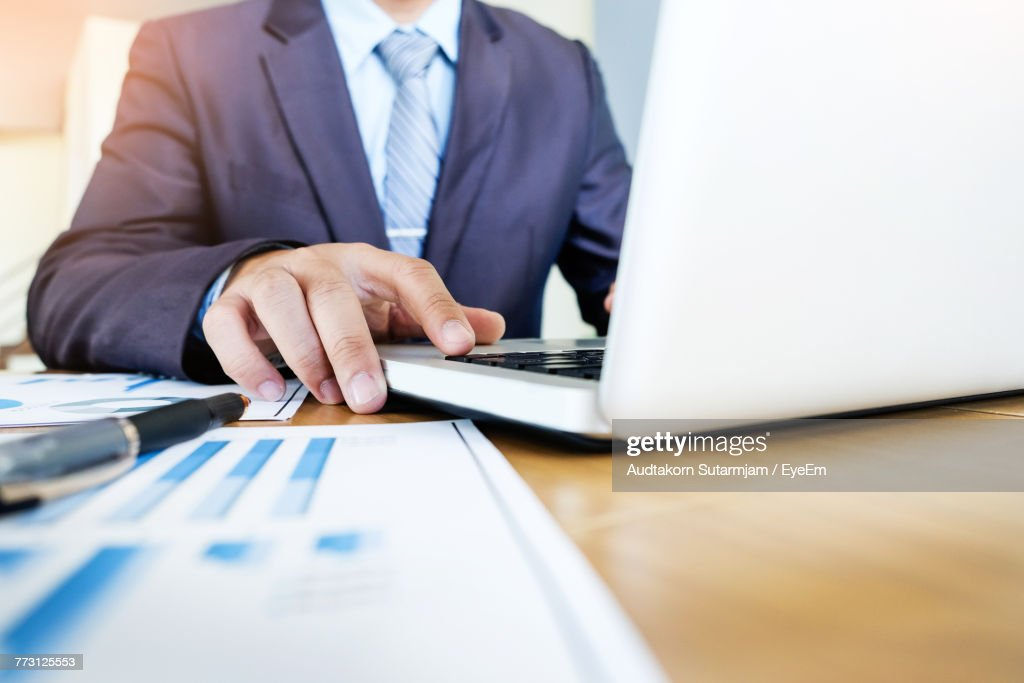 Midsection Of Businessman Using Laptop : Photo