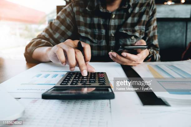 midsection of businessman using mobile phone and calculator at desk in office - tax stock pictures, royalty-free photos & images