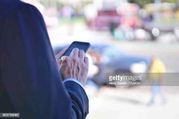 Midsection Of Businessman Using Mobile Phone