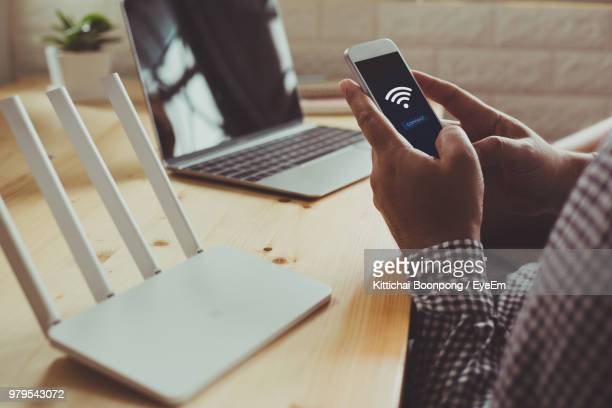 midsection of businessman using phone at desk - wireless technology foto e immagini stock