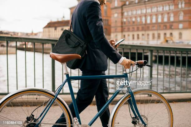 midsection of businessman using smart phone while walking with bicycle on bridge in city - city life bildbanksfoton och bilder