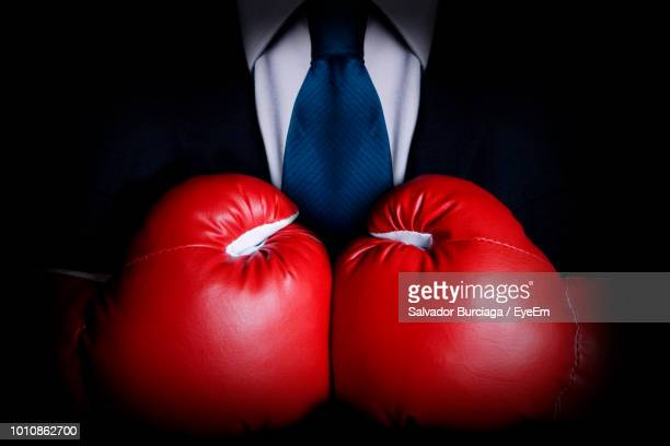 midsection of businessman wearing boxing gloves against black background - boxing gloves stock pictures, royalty-free photos & images