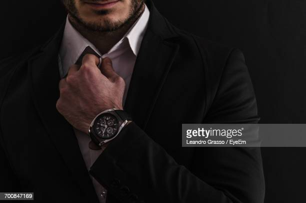 midsection of businessman wearing suit against black background - wrist watch stock pictures, royalty-free photos & images