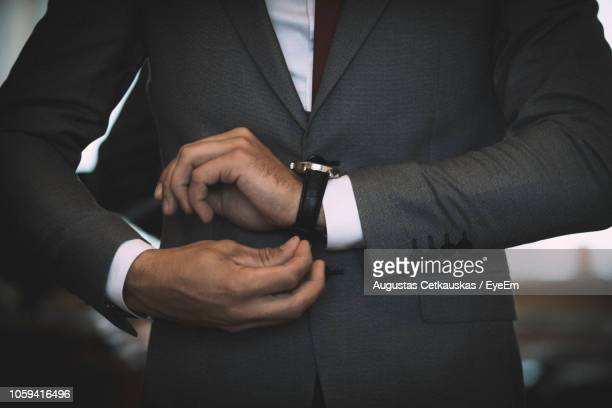 midsection of businessman wearing wristwatch - getting dressed stock pictures, royalty-free photos & images