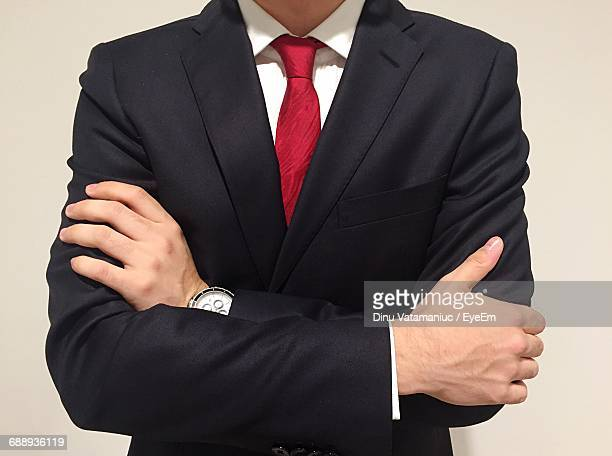 Midsection Of Businessman With Arms Crossed Against Beige Background
