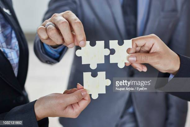 midsection of businessman with colleagues holding jigsaw pieces at office - tre persone foto e immagini stock